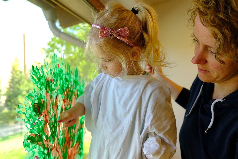 Foto: Ein Mädchen malt mit Fingerfarben einen Baum ans Fenster