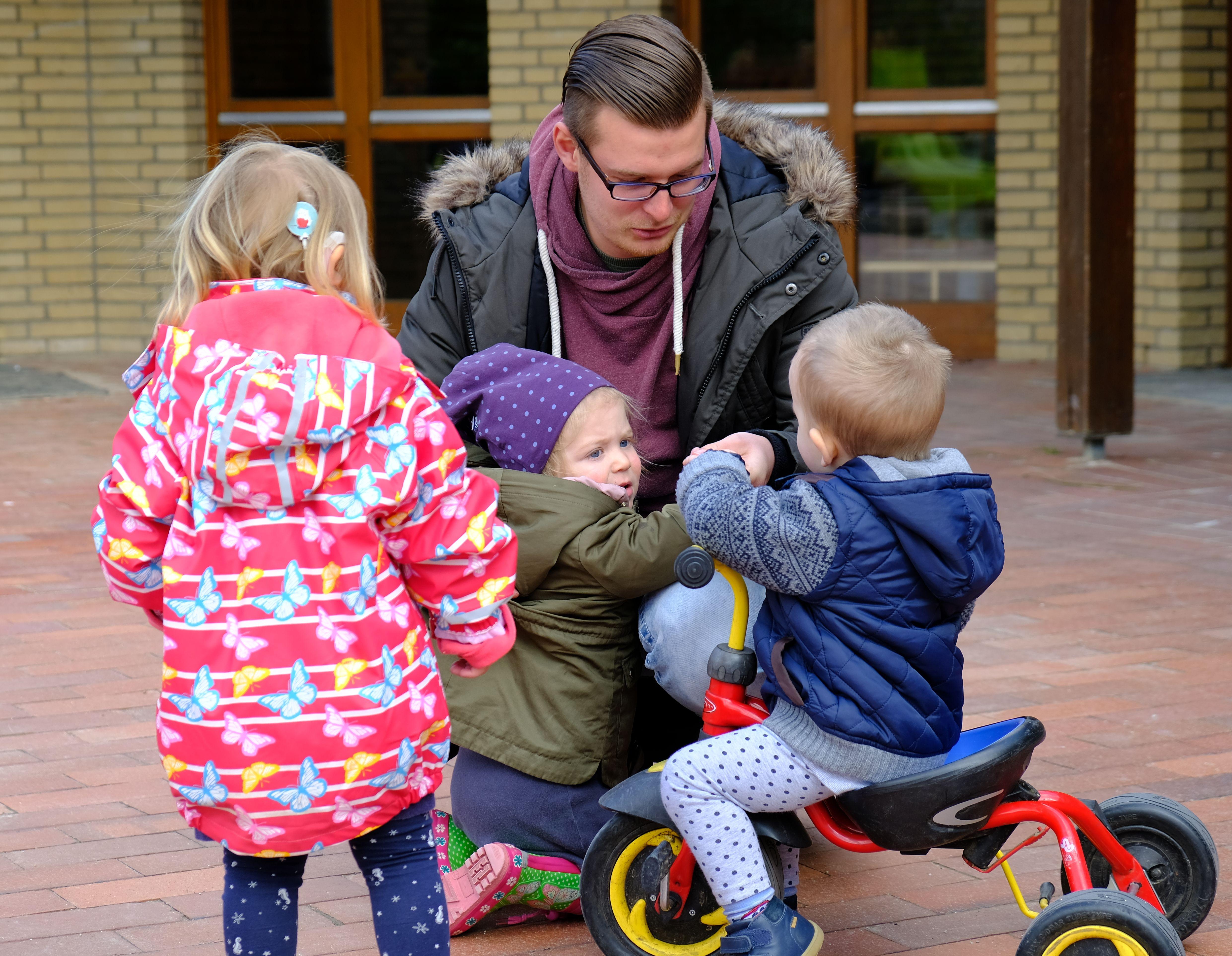 Foto: Ein Erzieher kümmert sich um drei Krippenkinder im Außengelände einer Kindertagesstätte
