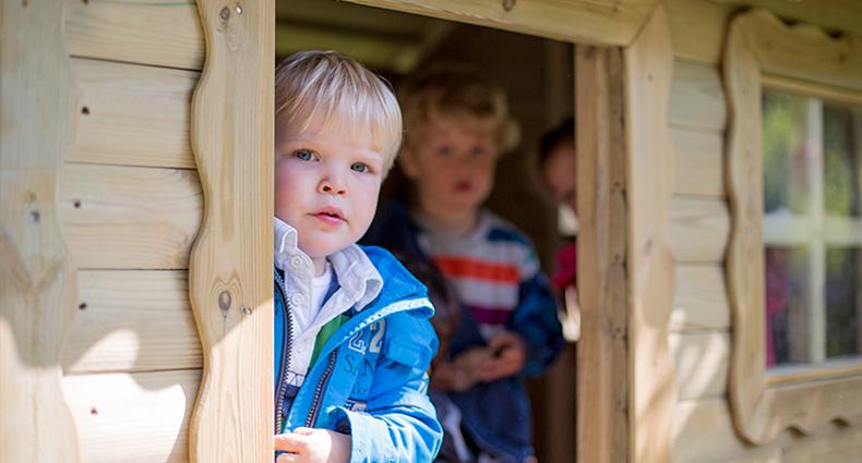 Foto: Eine Junge schaut aus einem Spielhaus